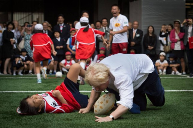 Mayor of London Boris Johnson joins a Street Rugby tournament in a Tokyo street with school children and adults from Nihonbashi, Yaesu & Kyobashi Community Associations, to mark Japan hosting 2019 Rugby World Cup where Mr Johnson is on the final day of his four day trade visit to Japan. PRESS ASSOCIATION Photo. Picture date: Thursday October 15, 2015. During the game the mayor knocked over 10 year old Toki Sekiguchi who was unharmed in the collision. See PA story POLITICS Johnson. Photo credit should read: Stefan Rousseau/PA Wire