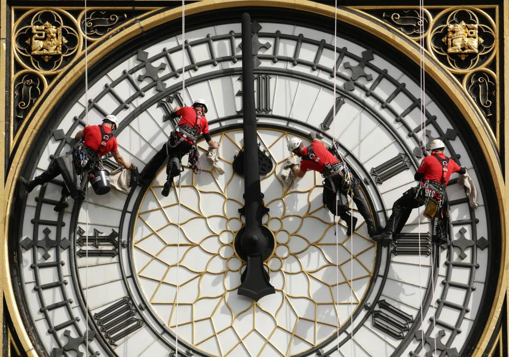"""File photo dated 18/08/14 of a specialist technical abseil team cleaning and inspecting one of the four faces of the Great Clock, otherwise known as Big Ben, at the Houses of Parliament in London, as the taxpayer faces a bill of up to £40 million to keep the famous """"bongs"""" of Big Ben sounding, according to a report. PRESS ASSOCIATION Photo. Issue date: Saturday October 17, 2015. Parliament's Great Clock is said to be so dilapidated that it could grind to a halt altogether unless drastic repairs are carried out. See PA story POLITICS Clock. Photo credit should read: Yui Mok/PA Wire"""