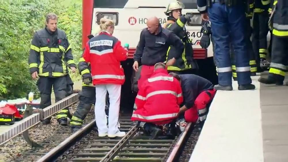 Pic shows: Firefighters helping the schoolboy who had his legs crushed under a train after being pushed onto the tracks by his mother.nnAn 11-year-old schoolboy who had his legs crushed under a train was pushed onto the tracks by his mother, say police.nnThe incident left the boy badly hurt under the wheels of the train despite the fact that the driver slammed on the emergency brakes but the station at Harvestehude in Hamburg, GermanynnMedics and fireman who went under the train so that the youngster was conscious the whole time despite horrific injuries.nnThey had to manoeuvre the boy and then push the train backwards by hand using rescue workers so that he could be given emergency treatment on the scene.nnThe spokesman confirmed that they had open investigation with the murder commission for attempted murder, although did not say whether this was based on eyewitnesses or video footage. They added that they are questioning the 31-year-old who they described as being psychologically disturbed after arresting her at the scene. She's been kept in a psychiatric hospital for the time being.nnThe 11-year-old schoolboy was taken to hospital with severe injuries.nnMeanwhile trained counsellors needed to be provided to give treatment to the other guests shocked by what they had seen.nn(ends)nn