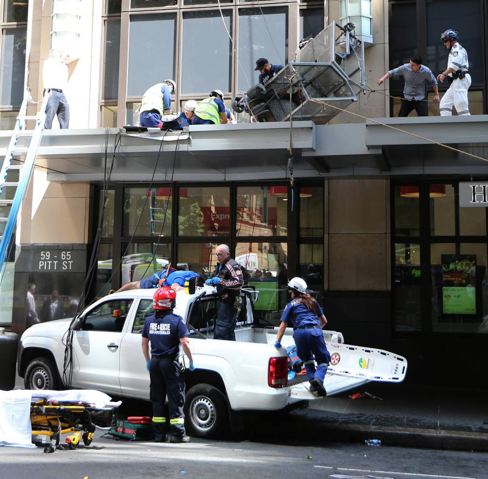 Emergency services help the two injured men who fell from a metal window cleaning cage in Sydney. Tuesday, Oct. 20, 2015. Two window cleaners have fallen about 12 storeys from a highrise building in Sydney's CBD after a cable reportedly snapped on their platform. (AAP Image/David Moir) NO ARCHIVING
