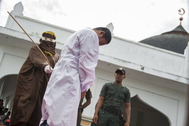 """An Acehnese man convicted for """"immoral acts"""" is lashed by a hooded local government officer during a public caning at a square in Banda Aceh, Aceh province, on June 12, 2015. AFP PHOTO / Chaideer MAHYUDDIN (Photo credit should read CHAIDEER MAHYUDDIN/AFP/Getty Images)"""