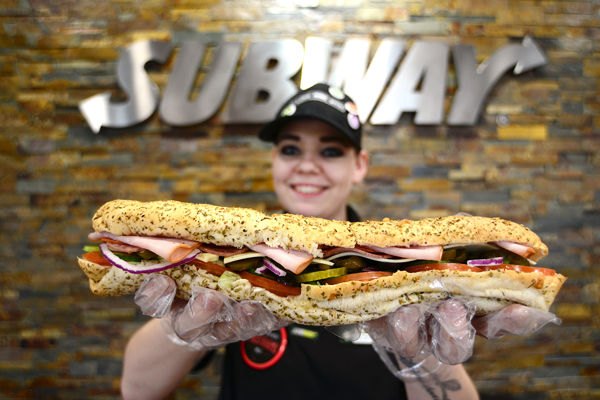 F29FE0 A Subway staff member holding a footlong sandwich. Picture: Scott Bairstow/Alamy
