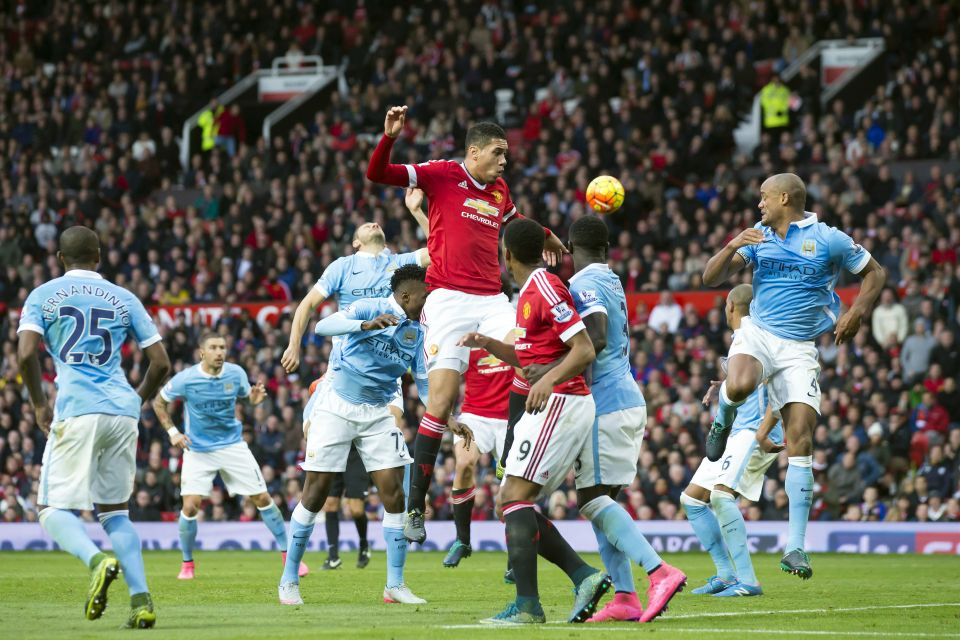 Manchester United's Chris Smalling, centre, challenges for the ball during the English Premier League soccer match between Manchester United and Manchester City at Old Trafford Stadium, Manchester, England, Sunday, Oct. 25, 2015. (AP Photo/Jon Super)