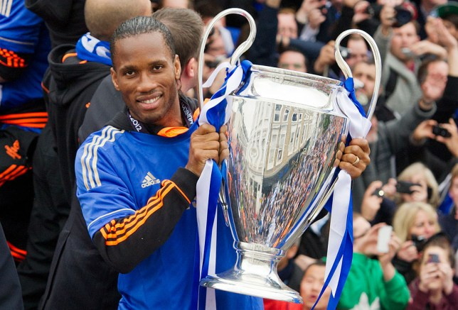 Chelsea football club player Didier Drogba holds the Champions League and FA Cup as the team rides during an open-top bus parade along Kings Road in west London on May 20, 2012. Chelsea's dramatic win over Bayern Munich on penalties last night has resulted in the first ever Champions League win for a London-based team. AFP PHOTO / LEON NEAL (Photo credit should read LEON NEAL/AFP/GettyImages)