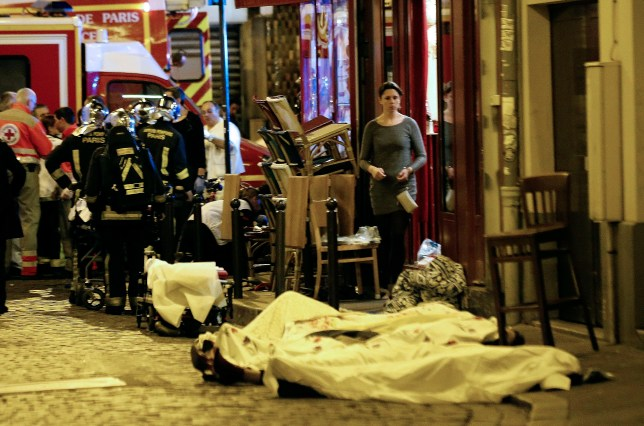A woman watches victims in the 10th district of Paris, Friday, Nov. 13, 2015. At least 35 people were killed Friday in shootings and explosions around Paris, many of them in a popular concert hall where patrons were taken hostage, police and medical officials said. (AP Photo/Jacques Brinon)