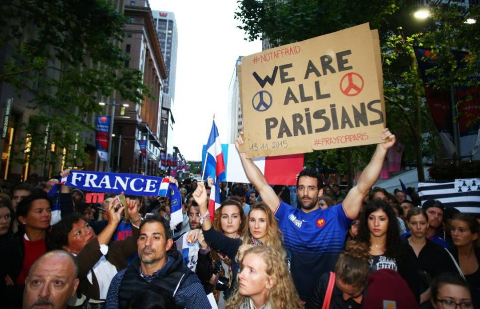 SYDNEY, AUSTRALIA - NOVEMBER 14: People hold uo placards during a vigil for victims of the Paris terror attacks at Martin Place on November 14, 2015 in Sydney, Australia. At least 120 people have been killed and over 200 injured, 80 of which seriously, following a series of terrorist attacks in the French capital. (Photo by Daniel Munoz/Getty Images)