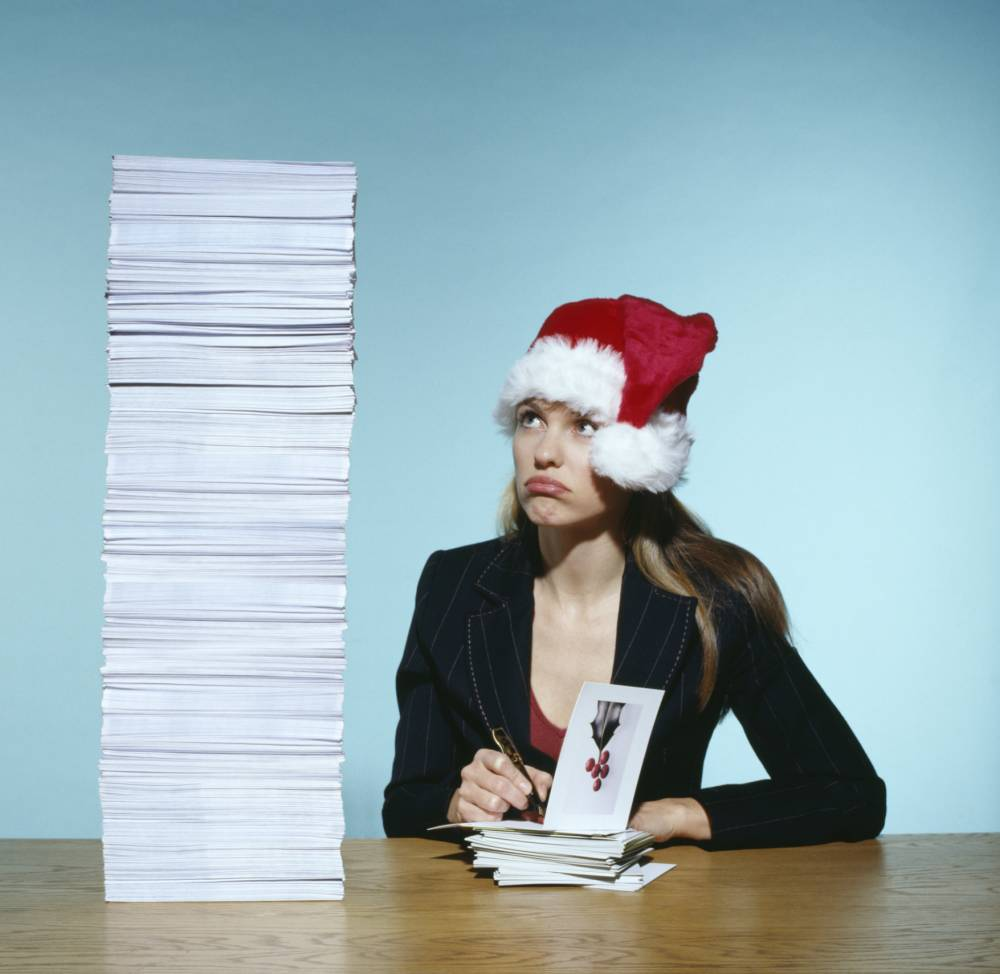 Woman wearing santa, by stack of xmas cards, writing in card