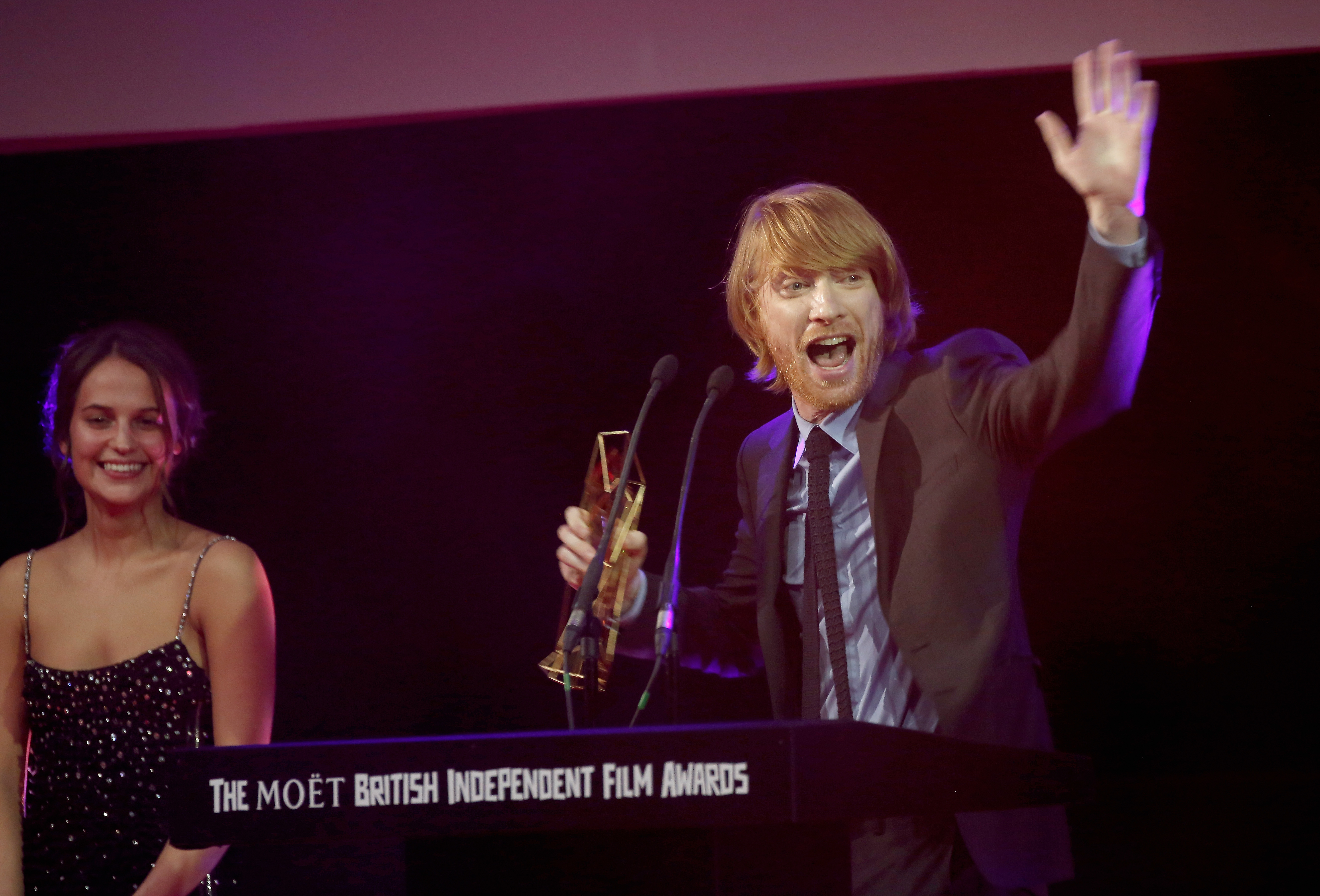 LONDON, ENGLAND - DECEMBER 06: Actress Alicia Vikander (L) and actor Domhnall Gleeson on stage as he accepts the award for Best Supporting Actor on behalf of his father Brendan Gleeson for his role in the film 'Brooklyn' at The Moet British Independent Film Awards 2015 on December 6, 2015 in London, United Kingdom. (Photo by John Phillips/Getty Images for The Moet British Independent Film Awards)