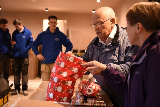 David Haylock (second right) and his wife Carol look at presents (Picture: PA)