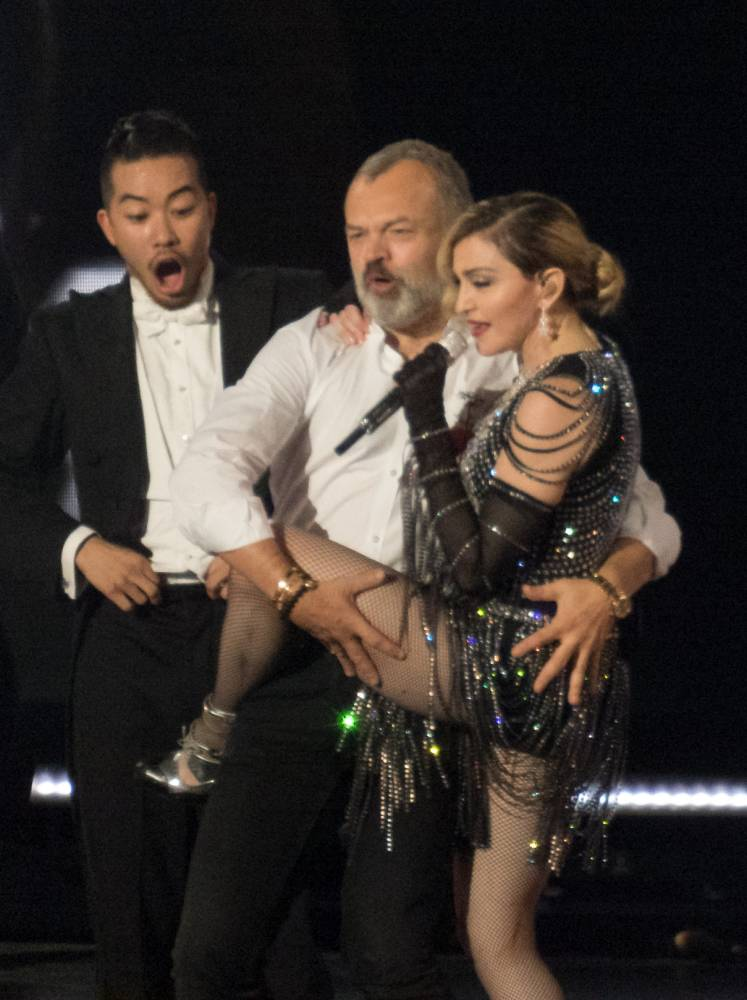 Graham Norton makes a surprise appearance on stage with Madonna during her concert at the O2 Arena in London