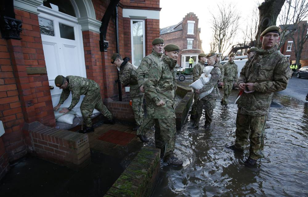 Members of the armed forces help distribute sandbags to residents following flooding in Carlisle. PRESS ASSOCIATION Photo. Picture date: Sunday December 6, 2015. The Environment Agency declared 130 flood warnings, while residents in some areas were evacuated from their homes. Rain continued to fall overnight in Scotland, northern England and northern parts of Wales, and is likely to continue for a few hours yet, forecasters said.See PA story WEATHER Winter. Photo credit should read: Owen Humphreys/PA Wire