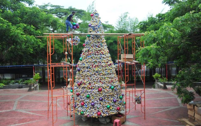 Mandatory Credit: Photo by Xinhua/REX/Shutterstock (5498391d) A worker decorates a Christmas tree made from tin cans of drinks at the Church of Santo Laurensius at Tangerang, Banten province, Indonesia Christmas tree made of tin cans, Church of Santo Laurensius, Tangerang, Banten province, Indonesia - 18 Dec 2015 A total of 10 thousand cans were donated by church members to make a Christmas tree with 8 meters high.