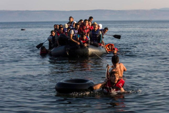FOR STORY GREECE STUCK IN CRISIS PHOTO GALLERY - In this photo taken on Monday, July 27, 2015, two migrants pull an overcrowded dinghy with Syrian and Afghan refugees arriving from the Turkish coast to the Greek island of Lesbos. Anyone hoping Greece might finally have a quiet year was quickly disappointed in 2015. Brinkmanship with bailout lenders brought the country a half-step from financial collapse and eurozone exit, while Greece was at the center of Europe's worst refugee crisis since World War II. (AP Photo/Santi Palacios)