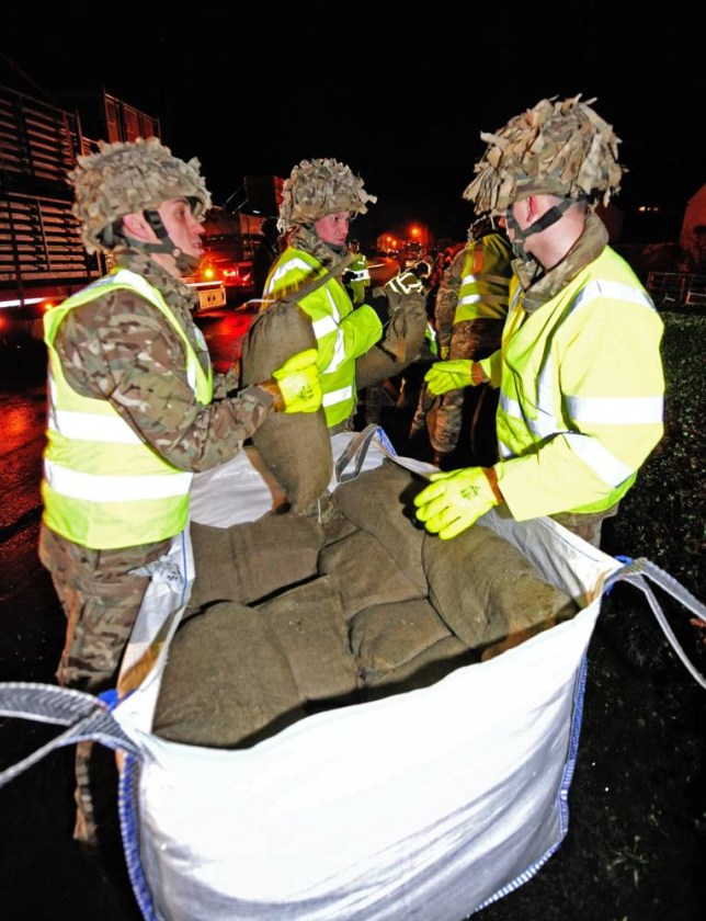 Troops from the Duke of Lancaster Regiment, 2nd Battalion, battle the weather and work through Christmas day night to erect flood defences in the Cumbrian village of Braithwaite which is in danger flooding.