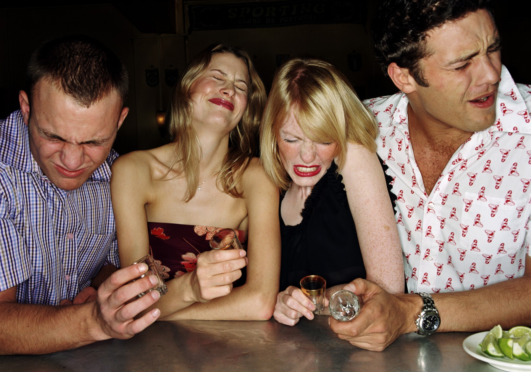 Four young friends drinking tequilla shots
