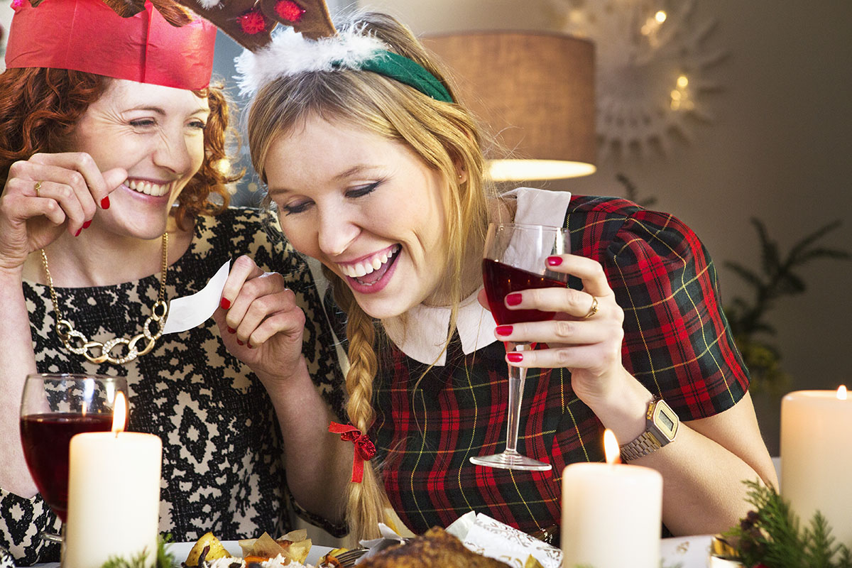 Christmas dinner drinking game Friends laughing at joke at Christmas dinner table Credit: Getty