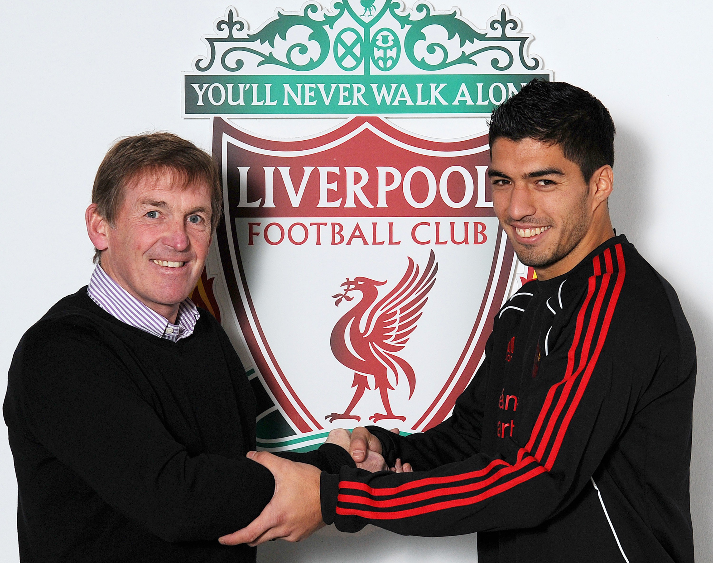 LIVERPOOL, ENGLAND - JANUARY 29: (THE SUN OUT) ***EXCLUSIVE COVERAGE*** (MINIMUM USAGE FEE APPLIES PER IMAGE - 250 GBP OR LOCAL EQUIVALENT AND ONLINE RATE 125 GBP OR LOCAL EQUIVALENT) Luis Suarez (R) of Liverpool shakes hands with Kenny Dalglish manager of Liverpool at Melwood training ground on January 29, 2011 in Liverpool, England. (Photo by John Powell/Liverpool FC via Getty Images)