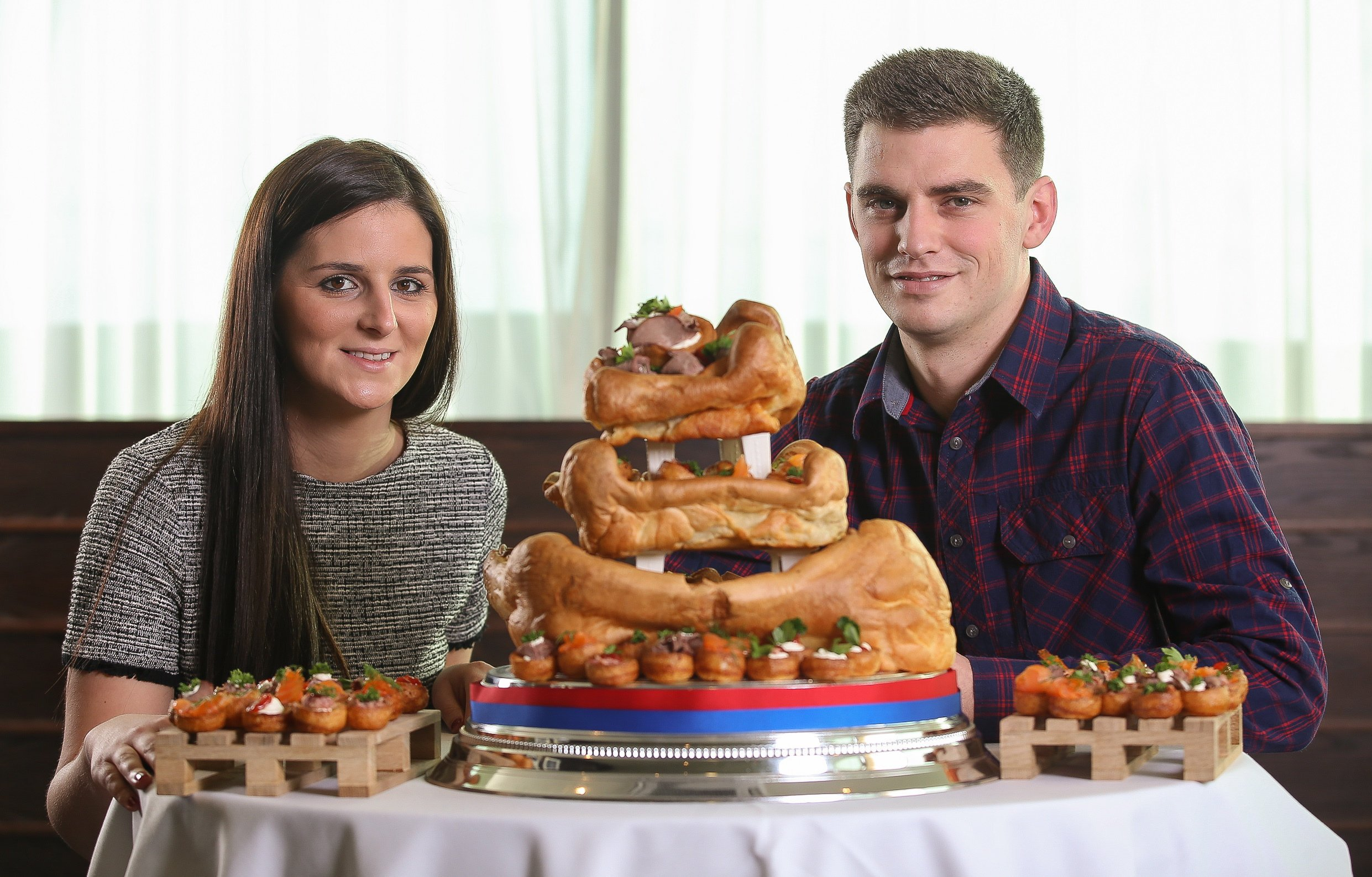 Adam Nicholson and Becca Piwinksi of Beverley, East Yorkshire who have won the ultimate northern wedding cake - made from YORKSHIRE PUDDINGS. See Ross Parry copy RPYPUD : A couple preparing for wedded bliss have won the ultimate northern wedding cake - made from YORKSHIRE PUDDINGS. Adam Nicholson and Becca Piwinski will be treating their guests to the deliciously different wedding cake on their big day in July on a Yorkshire farm. The lucky pair won the battered delight, created by experts at Aunt Bessieís, in a competition to celebrate National Yorkshire Pudding Day on Sunday. The three-tiered pud features delicate Yorkshire pudding canapÈs and even has a gravy fountain. Bride-to-be Becca said: ìWe are getting married on a Yorkshire farm and a giant Yorkshire pudding wedding cake felt like a brilliant idea to wow our guests with.