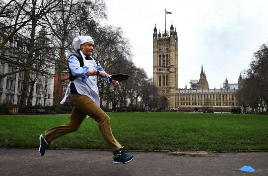 epa05151048 An MP (member of parliament) races around Victoria Gardens outside the Houses of Parliament while tossing his pancake in London, Britain, 09 February 2016. MPs from the Lords, Commons and the media took part in the annual Shrove Tuesday pancake race to raise money for charity. EPA/ANDY RAIN