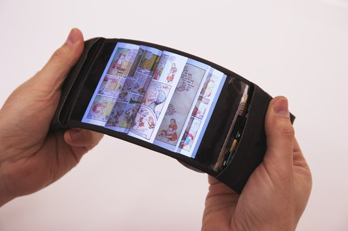 """Queen's University's Human Media Lab to unveil world's first wireless flexible smartphone; simulates feeling of navigating pages via haptic bend input KINGSTON - Researchers at Queen's University's Human Media Lab have developed the world's first full-colour, high-resolution and wireless flexible smartphone to combine multitouch with bend input. The phone, which they have named ReFlex, allows users to experience physical tactile feedback when interacting with their apps through bend gestures. """"This represents a completely new way of physical interaction with flexible smartphones"""" says Roel Vertegaal (School of Computing), director of the Human Media Lab at Queen's University. """"When this smartphone is bent down on the right, pages flip through the fingers from right to left, just like they would in a book. More extreme bends speed up the page flips. Users can feel the sensation of the page moving through their fingertips via a detailed vibration of the phone. This allows eyes-free navigation, making it easier for users to keep track of where they are in a document."""" ReFlex is based on a high definition 720p LG Display Flexible OLED touch screen powered by an Android 4.4 """"KitKat"""" board mounted to the side of the display. Bend sensors behind the display sense the force with which a user bends the screen, which is made available to apps for use as input. ReFlex also features a voice coil that allows the phone to simulate forces and friction through highly detailed vibrations of the display. Combined with the passive force feedback felt when bending the display, this allows for a highly realistic simulation of physical forces when interacting with virtual objects. """"This allows for the most accurate physical simulation of interacting with virtual data possible on a smartphone today,"""" says Dr. Vertegaal. """"When a user plays the """"Angry Birds"""" game with ReFlex, they bend the screen to stretch the sling shot. As the rubber band expands, users experience vibrations that simulat"""