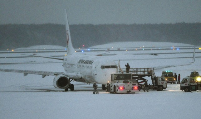 A Japan Airlines Boeing 737 sits on the snow-covered tarmac after more than 160 passengers and crew slid down emergency chutes in snow due to an engine fire at New Chitose Airport in Sapporo in Hokkaido, Japan's northernmost main island. Japanese media said the engine fire forced the domestic flight with 159 passengers and six crew members bound for Fukuoka in southern Japan to abort takeoff and smoke entered the cabin. (Daisuke Suzuki/Kyodo News via AP) JAPAN OUT, MANDATORY CREDIT