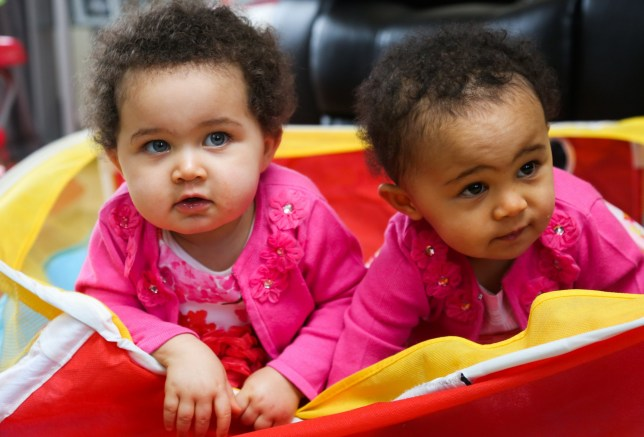 Identical sisters Amelia (right) and Jasmine - who have different skin an eye colour. See SWNS story SWTWINS; A mum has told how her one-year-old daughters get mistaken for step-sisters ñ despite the fact theyíre identical twins. During her pregnancy, Libby Appleby, 37, and her partner Tafadzwa Madzimbamuto, 40, were warned their twins would look so alike they would need to ëmark them with inkí to tell them apart. So they were shocked when their twins arrived in February 2015 - with contrasting skin tones. While elder twin Amelia has dark skin, black hair and brown eyes, her sister Jasmine has fair skin, blue eyes and mousey curls. Full-time mum Libby says: ìWe were flabbergasted, even the doctors couldnít believe it. ìThey look like theyíre different races.