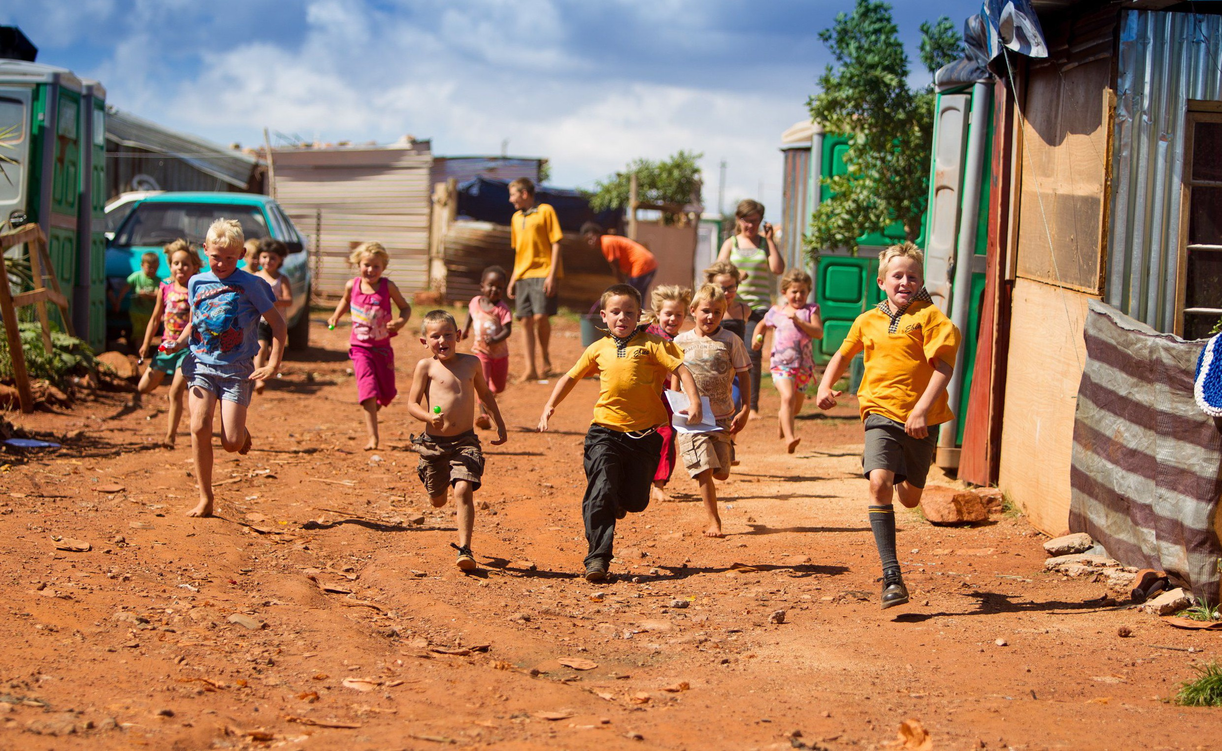 Pictured: Children playing in the camp. These white South African families are so poor they are forced to live in slums similar to the worst days of Apartheid. At this 'white squatter camp', hundreds of families have no power, barely any food or water and must live in poor shelter. Townships like this, which can be found all across the country, are a direct result of white poverty following Apartheid - which came to an end 22 years ago. Under the old white supremacist regime, which ended in 1994, the Afrikaners were almost guaranteed employment and housing. SEE OUR COPY FOR MORE DETAILS. Please byline: James Cheadle/Solent News © James Cheadle/Solent News & Photo Agency UK +44 (0) 2380 458800