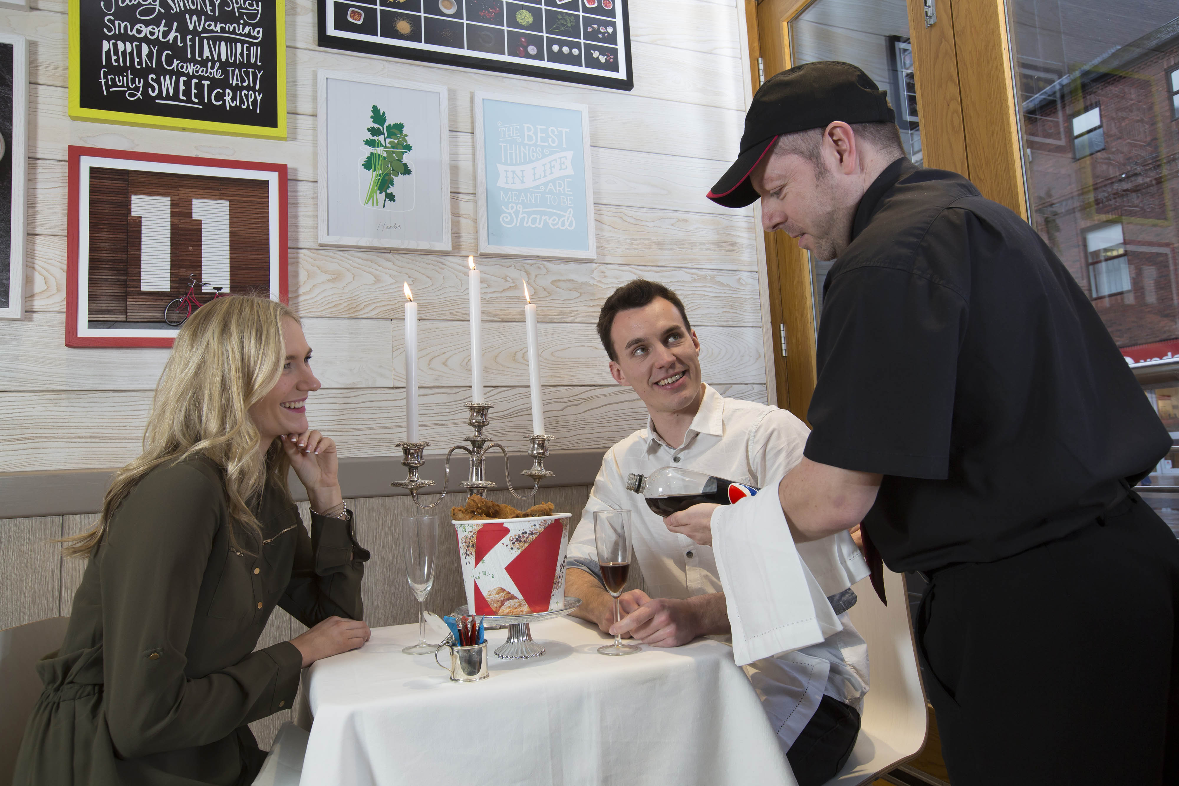 EDITORIAL USE ONLY The soft drink sommelier pours for Hattie and Tom at the KFC date night table.