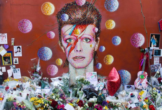(FILES) This file photo taken on January 15, 2016 shows floral tributes placed in front of a mural of British singer David Bowie, painted by Australian street artist James Cochran, aka Jimmy C, in Brixton, south London. David Bowie, who died on January 10, 2016, never performed in Warsaw, but the Polish capital aims to pay tribute to the famous singer by dedicating a giant mural painting to him. The result of a competition is expected to be announced on March 10, 2016. / AFP / JUSTIN TALLIS / RESTRICTED TO EDITORIAL USE - MANDATORY MENTION OF THE ARTIST UPON PUBLICATION - TO ILLUSTRATE THE EVENT AS SPECIFIED IN THE CAPTIONJUSTIN TALLIS/AFP/Getty Images