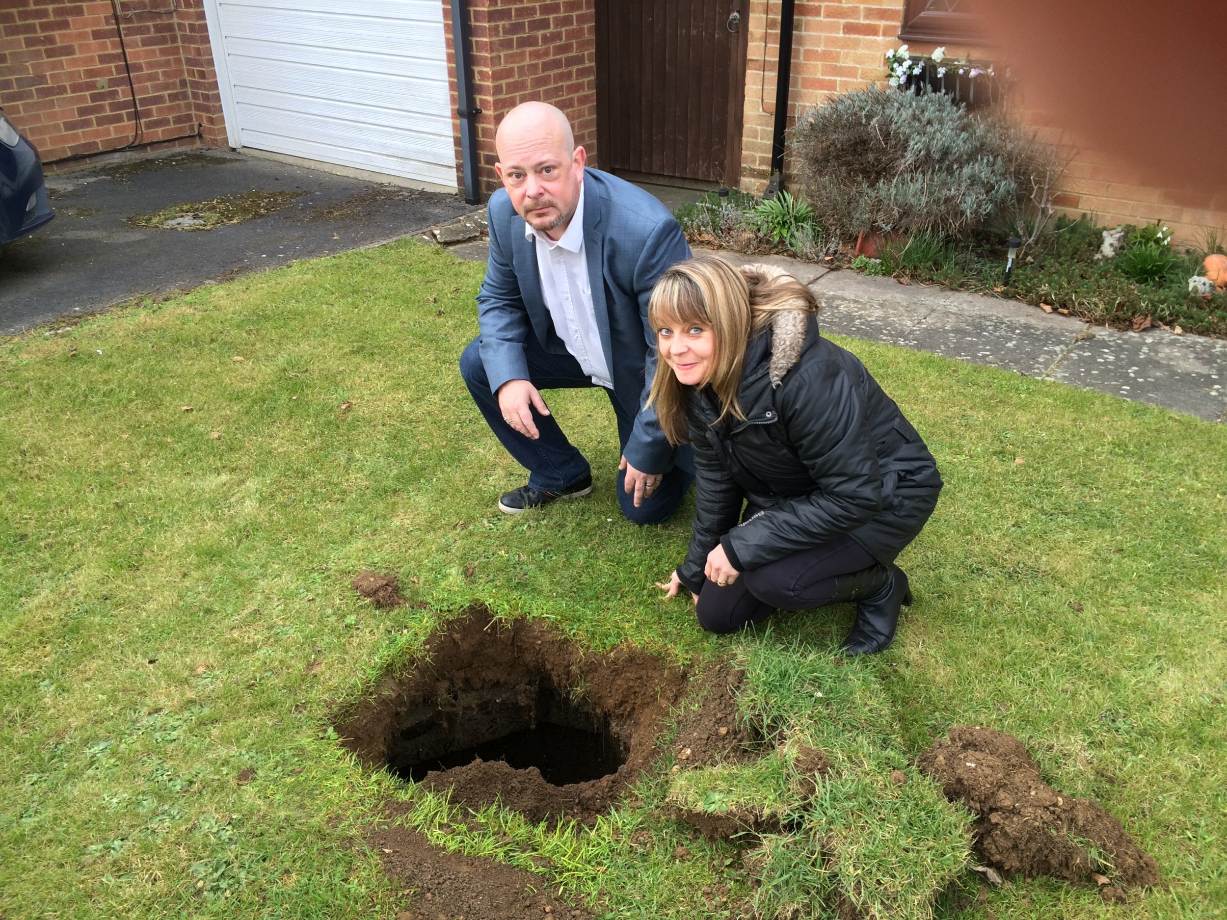 Kevin and Emma James who found a hole in their front garden. See Masons copy MNHOLE: A family have been left baffled after a deep hole opened up on their front lawn with rusty steps leading into the darkness. The more than two metre deep hole appeared when home owner Emma James was mowing the lawn but the cause is still a mystery. There are a few rusty steps steps leading down into the dark two by two feet hole which currently isn't big enough to squeeze down. Emma, 44, and her husband Kevin, 48, even contacted the company who built the house back in 1984 with no luck of finding out what the hole leads to.