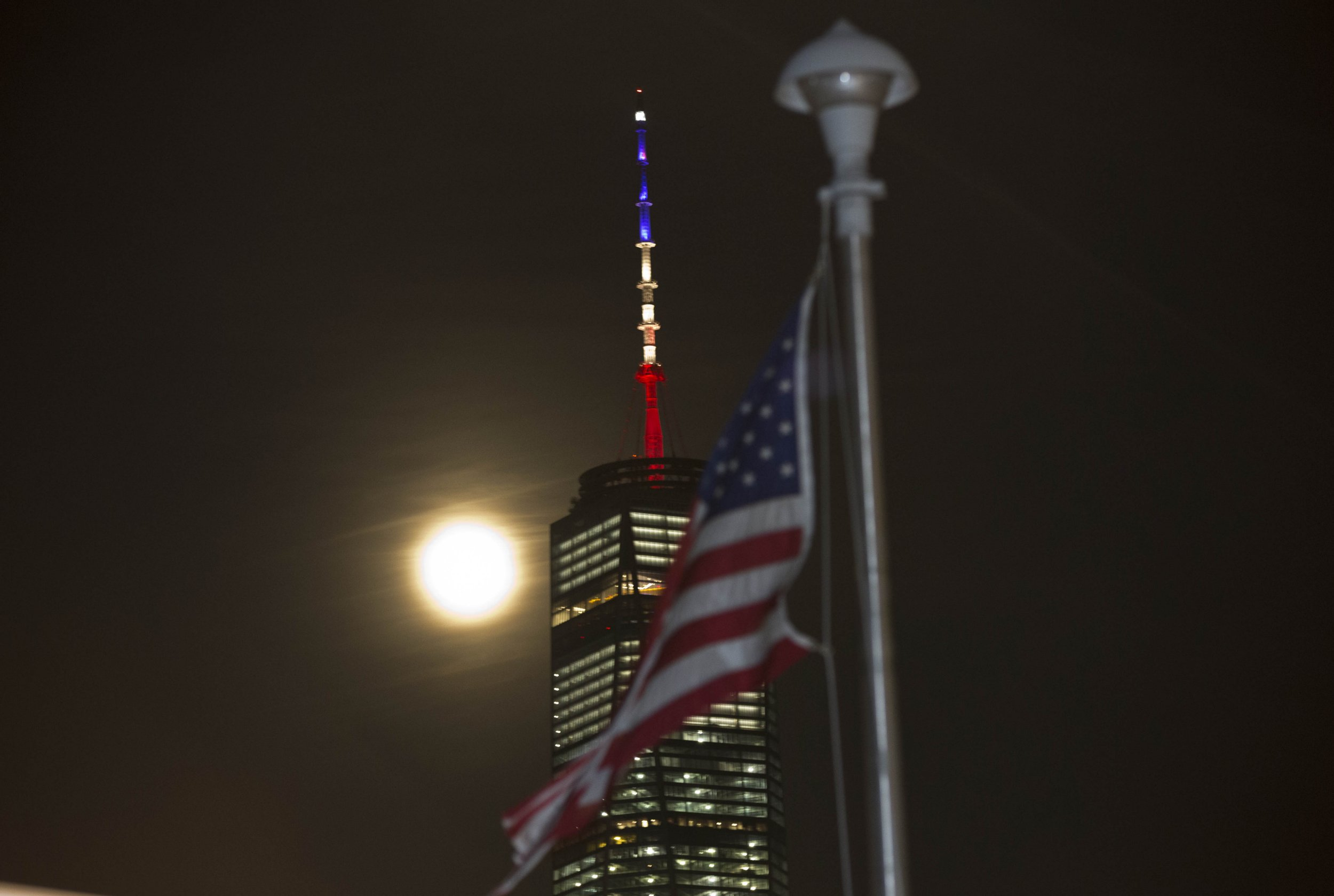 The full moon rises behind One World Trade Center on March 22, 2016 in New York, it's mast displaying the colors of the Belgian flag in a show of support following the terrorist attacks in Brussels. But the tribute from the tallest building in the United States, built on the site of the 9/11 attacks in New York, sparked confusion after a series of published photographs showed the colors to be blue, white and red -- those of the French flag -- that lit up the Trade Center after the November attacks in Paris. An AFP photographer said the colors on the World Trade Center appeared correct to the naked eye, but did not translate accurately in the camera, due to being shot against the dark night-time sky. / AFP PHOTO / TREVOR COLLENSTREVOR COLLENS/AFP/Getty Images