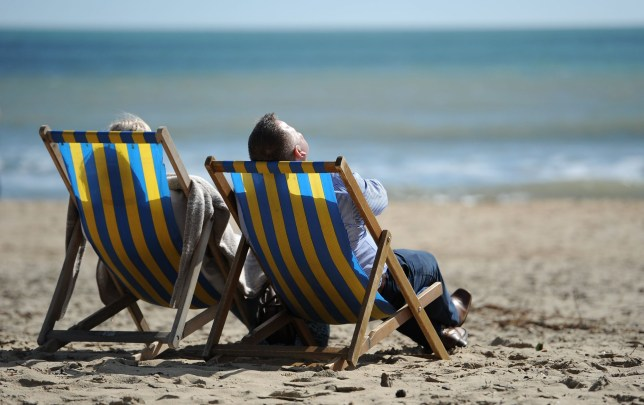 People enjoying the sun sitting in deckchairs on Bournemouth beach. PRESS ASSOCIATION Photo. Picture date: Friday March 25, 2016. See PA story WEATHER Easter. Photo credit should read: Andrew Matthews/PA Wire
