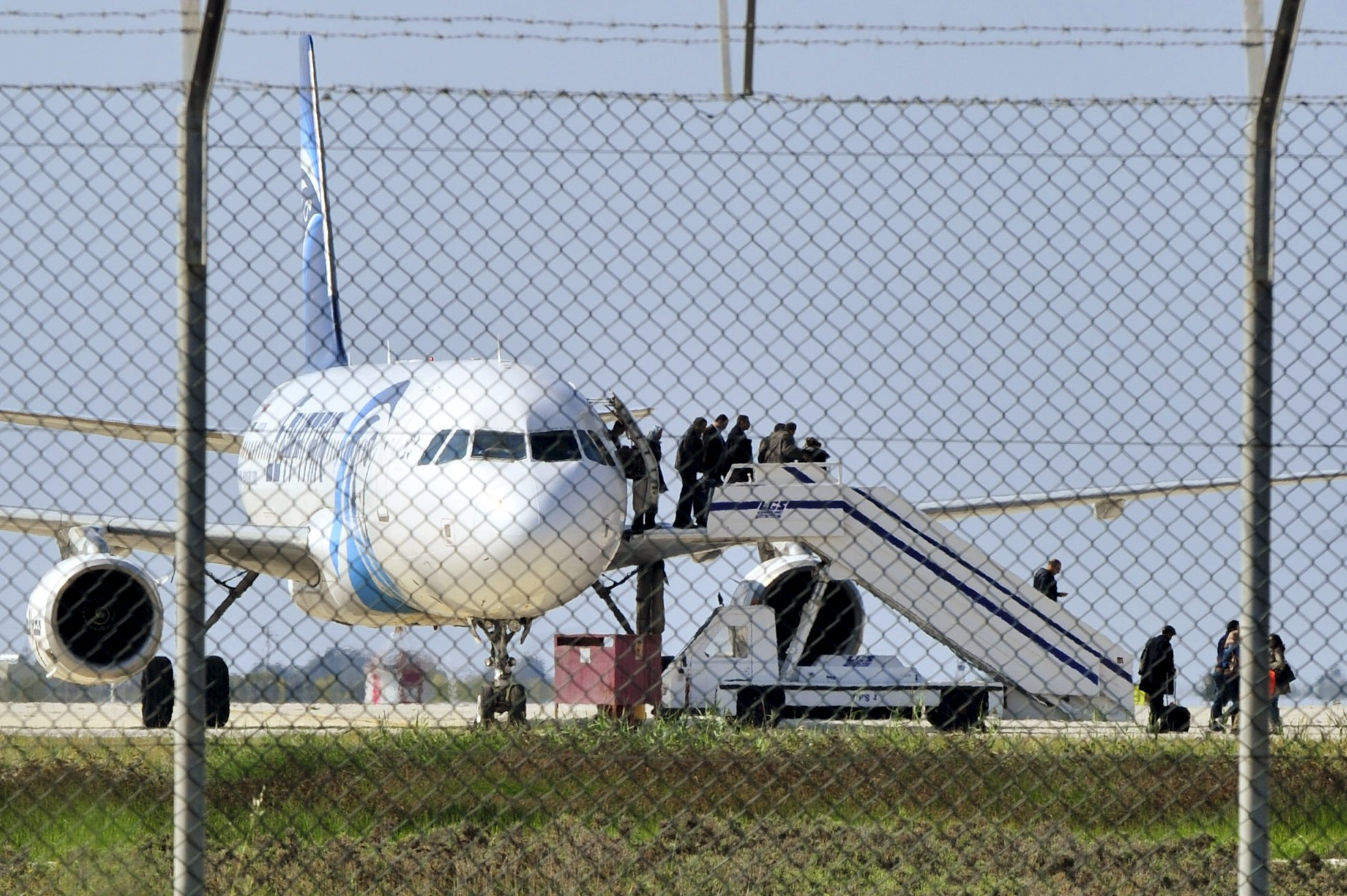 Passengers evacuate a hijacked EgyptAir Airbus 320 plane at Larnaca airport, Cyprus, March 29, 2016. REUTERS/Yiannis Kourtoglou