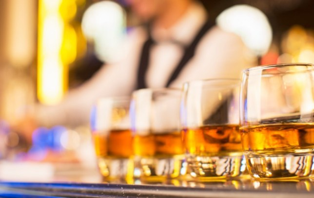 Close up of bourbon in glasses in a row on bar