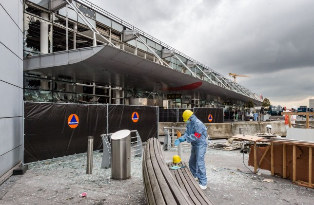 FILE - In this March 23, 2016 file photo, a forensics officer works in front of the damaged Zaventem Airport terminal in Brussels. It's unclear when the Brussels Airport will reopen, even after a meeting Friday, April 1 by Prime Minister Charles Michel and key members of the government.(AP Photo/Geert Vanden Wijngaert, Pool)