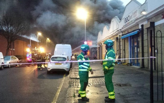 """London Ambulance HART handout photo of emergency personnel attending the blaze at an industrial bakery in Tottenham, north London. PRESS ASSOCIATION Photo. Picture date: Saturday April 2, 2016. The building, a single-storey industrial unit is """"100% alight"""", a spokeswoman for London Fire Brigade said. The front of the building has partially collapsed, but no-one is believed to be injured, she added. See PA story FIRE Tottenham. Photo credit should read: London Ambulance HART/PA Wire NOTE TO EDITORS: This handout photo may only be used in for editorial reporting purposes for the contemporaneous illustration of events, things or the people in the image or facts mentioned in the caption. Reuse of the picture may require further permission from the copyright holder."""