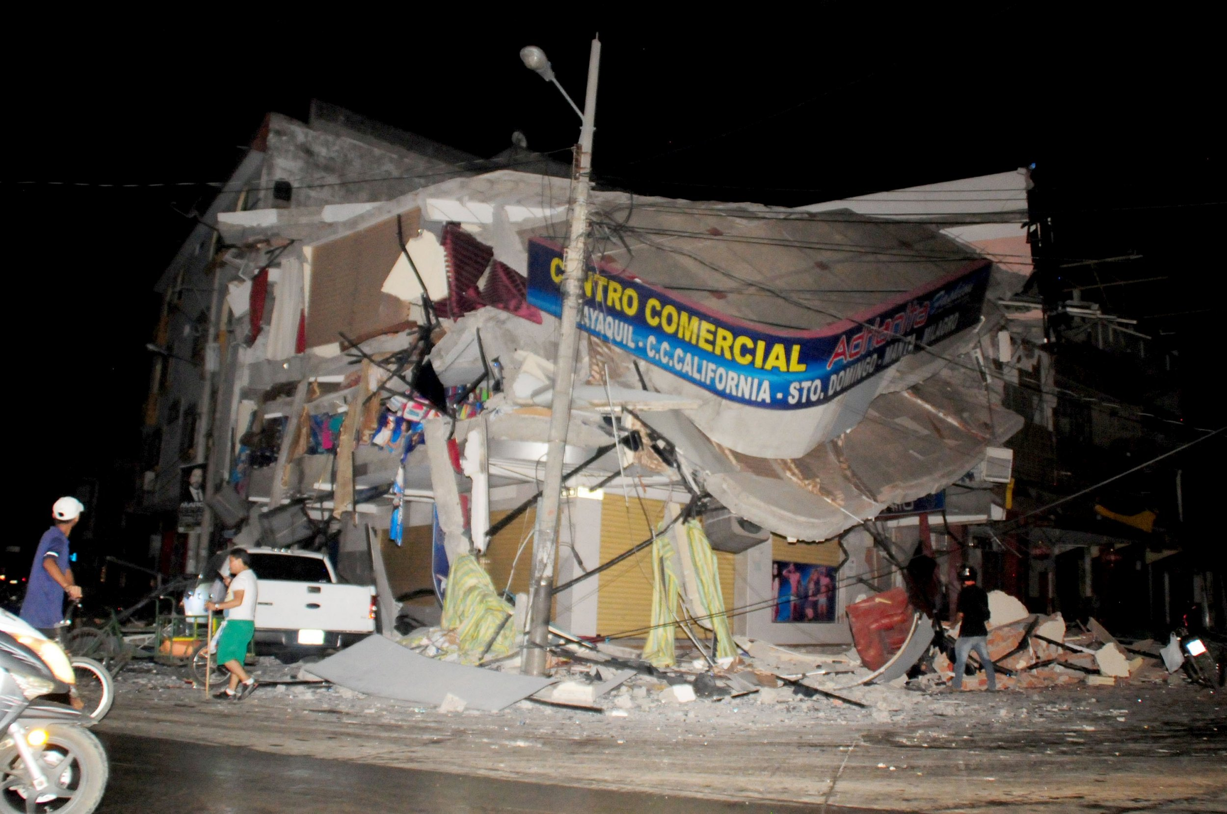 People walk near a damaged house after an earthquake struck off the Pacific coast in Manta, Ecuador, April 16, 2016. REUTERS/Paul Ochoa EDITORIAL USE ONLY. NO RESALES. NO ARCHIVE