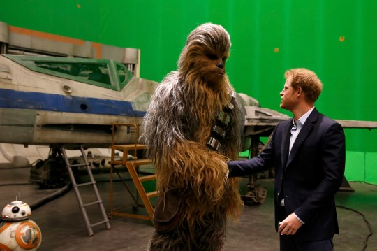 Britain's Prince Harry meets Chewbacca during a visit to the Star Wars film set at Pinewood Studios near Iver Heath, west of London, Britain, April 19, 2016. Prince William and Prince Harry are touring Pinewood to visit the production workshops and meet the creative teams working behind the scenes on the Star Wars films. REUTERS/Adrian Dennis/Pool