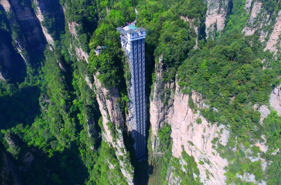 Mandatory Credit: Photo by Imaginechina/REX/Shutterstock (5658972d) Aerial view of the Bailong Elevator, also known as the Hundred Dragons Elevator Bailong Elevator, which is the tallest outdoor elevator in the world, Hunan province, China - 21 Apr 2016 The Bailong Elevator, also known as the Hundred Dragons Elevator, carries tourists 1,070ft (330m) up the side of a massive sandstone column in a mountain range in China's Hunan province. Riding the glass lift, which carries up to 50 people at a time or 1,380 an hour, offers jaw-dropping, not to say vertiginous, views down to the bottom of the rocky mountain range in the Wulingyuan area of Zhangijiajie. Work began on the lift, which cost 120m yuan in 1999 and finished in 2002. Bailong Elevator has set three Guinness world Records i.e. World's tallest full-exposure outdoor elevator, world's tallest double-deck sightseeing elevator and world's fastest passenger traffic elevator with biggest carrying capacity but due to the potential harm caused to the surrounding landscape, its future remains uncertain.