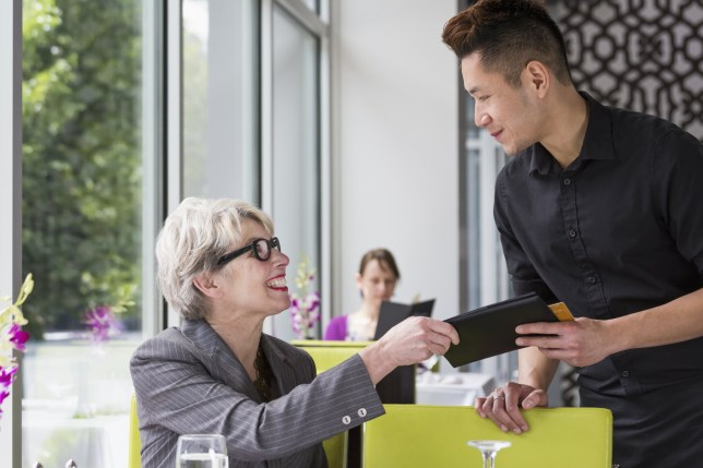 Businesswoman paying tab in restaurant