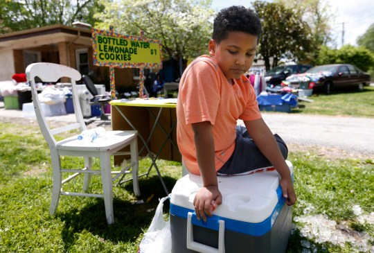 In this April 22, 2016 photo, Tristan Jacobson sits on a water cooler in front of his lemonade stand outside his home in Springfield, Mo. Tristan has been living with with Donnie and Jimmy Davis, who have been Tristan's kinship guardians. They have been holding a yard sale and set up a lemonade stand to raise money for his adoption. (Andrew Jansen/The Springfield News-Leader via AP) NO SALES; MANDATORY CREDIT