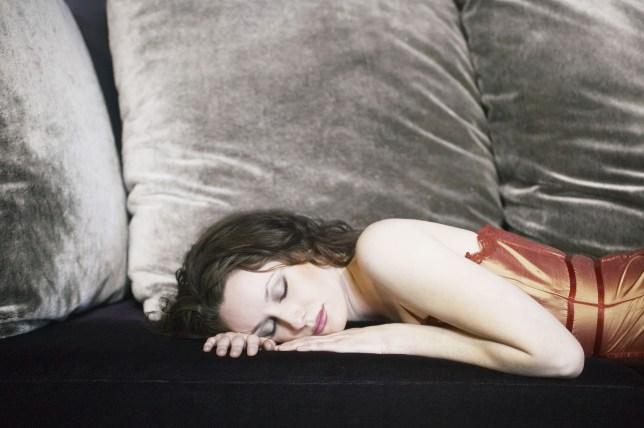 Woman falling asleep on sofa