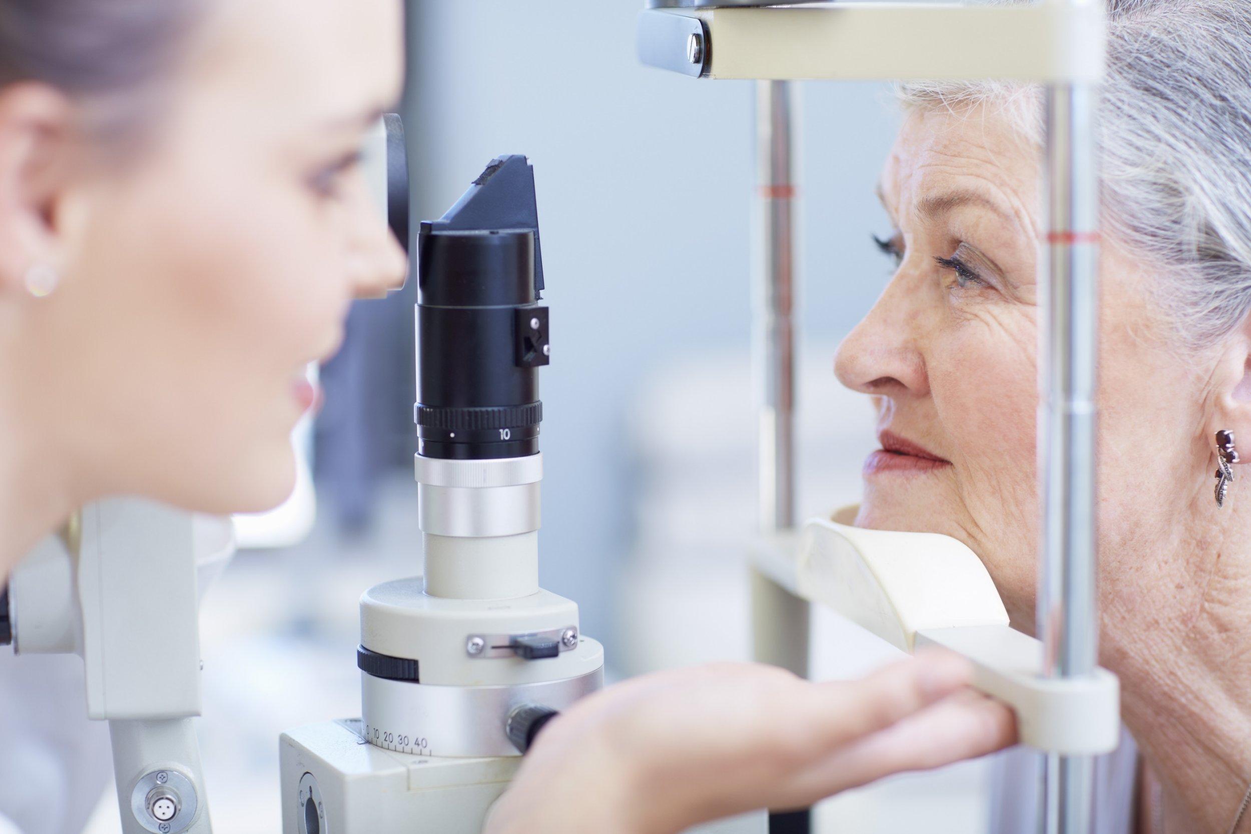 Eye doctor examining senior woman's vision