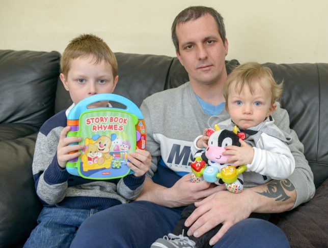 "Phillip Abbott, 32, with his sons Kayden, one, and Riley six holding the book that says the word ìCockî instead of the word clock. See SWNS story SWBOOK; A dad has told of his horror after he heard his one-year-old's Fisher-Price interactive book apparently teach his son the alphabet with the phrase: ""C for cock"". Phillip Abbott, 32, and his partner Kirsty Halsey, 28, were speechless when their eldest lad Riley, six, came out with the rude phrase. When his worried parents questioned him, they were astonished when he said he had learned it from his little brother Kayden's interactive book."