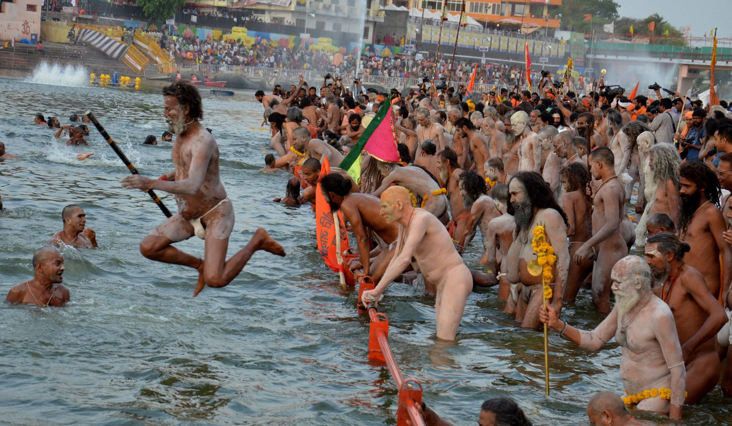 epaselect epa05320617 Naga Sadhu or 'Naked Holy Men' bathe in the Shipra river as they take part in the Simhastha Kumbh Mela festival in Ujjain, some 180 km from Bhopal, India, 21 May 2016. Kumbh Mela is a mass Hindu pilgrimage which occurs every twelve years, and there are several auxiliary events, including the Simhastha Kumbh Mela, which held more frequently and rotate among four locations. According to traditions, the event offers Hindu devotees the chance to wash away their sins with a ritual bath in the holy waters of one of the holy river that the festivals take place near. The Simhastha Kumbh Mela is being held from 22 April to 21 May.ø EPA/SANJEEV GUPTA