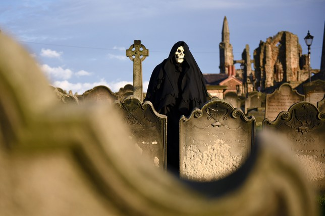 A man dressed as the Grim Reaper poses for pictures during the biannual Whitby Goth Weekend (WGW) festival in 2014 (PictureL AFP/Getty Images)