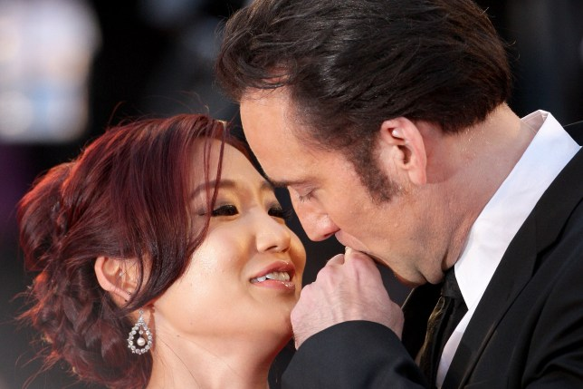 VENICE, ITALY - AUGUST 30: Actor Nicolas Cage removes lipstick from his mouth after kissing his wife Alice Kim Cage at the 'Joe' Premiere during The 70th Venice International Film Festival at Palazzo Del Cinema on August 30, 2013 in Venice, Italy. (Photo by Franco Origlia/Getty Images)