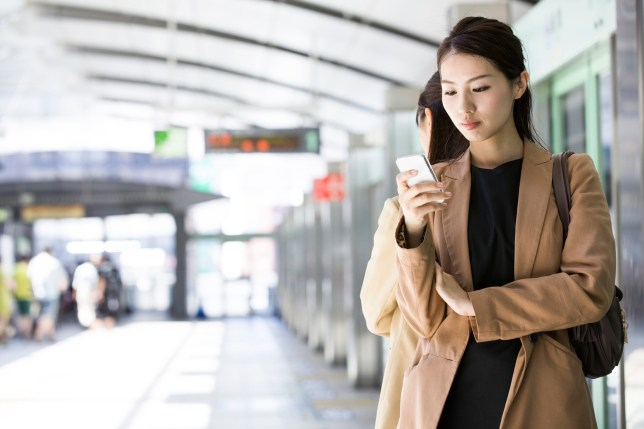 businesswoman checking a smart phone at station