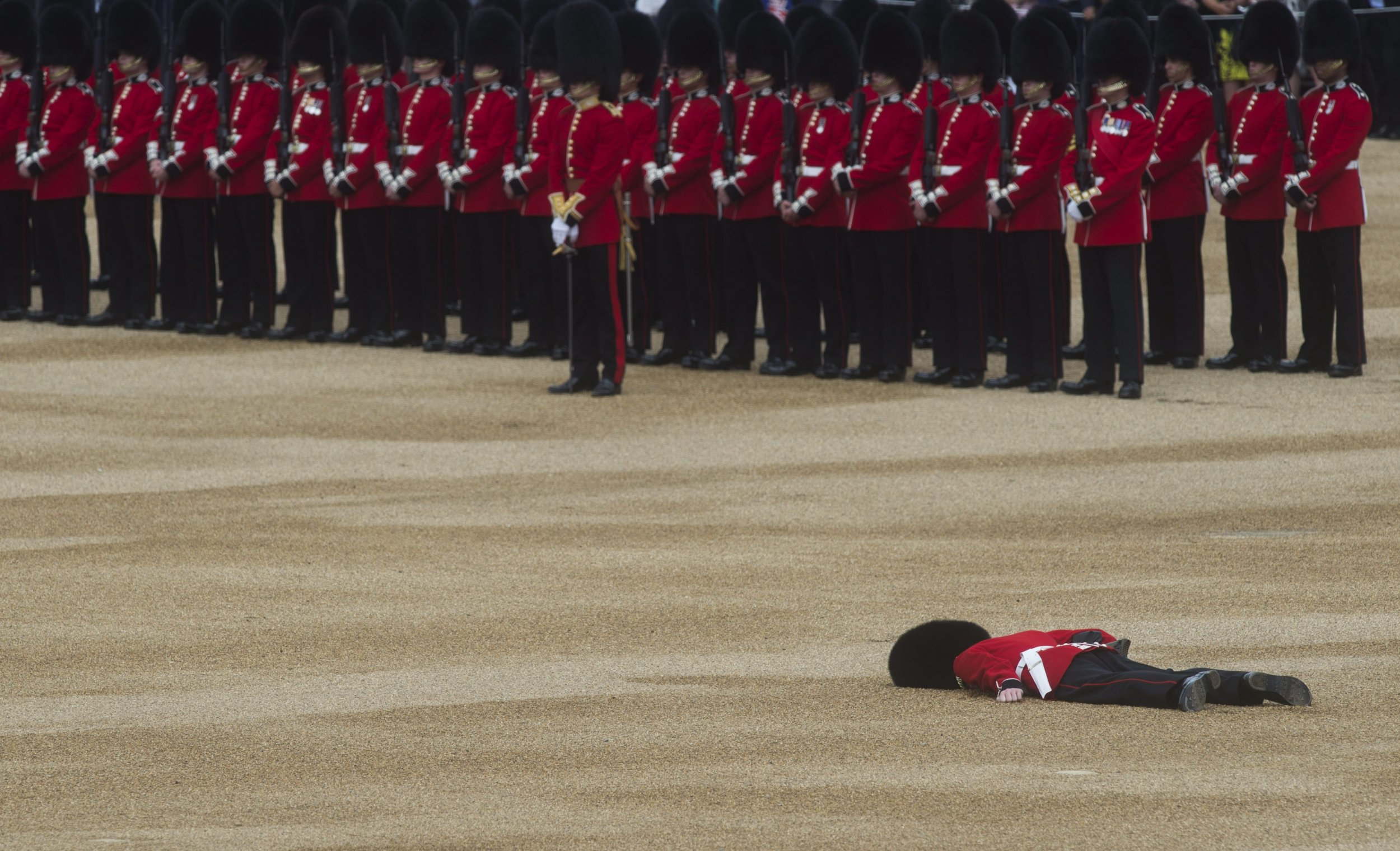 epa05356713 A guardsman collapses during the Trooping of the Color Queen's 90th birthday parade on Horse Guards Parade, central London, Britain, 11 June 2016. The annual Queenís Birthday Parade is more popularly known as Trooping the Color, when the Queenís Color is 'Trooped' in front of Her Majesty and all the Royal Colonels. EPA/WILL OLIVER