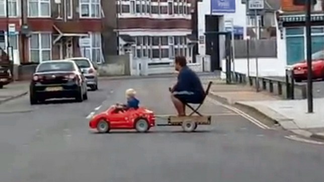 Video grab of the moment a dad was towed home by his son - driving a mini car. See MASONS story MNMINI; THIS is the hilarious moment a young lad is spotted behind the wheel of a mini-car - as he tows his dad back on home on a trailer. The mini-motorist was spotted in the centre of Bognor Regis, West Sussex, last Sunday by bemused passers-by. A short video of the comical scene shows a blonde-haired boy sitting in a little red electric car and towing his dad behind him. The dad is sitting on a chair on top of the trailer and can be see pushing the button on a pedestrian crossing before the pair cross a busy road.